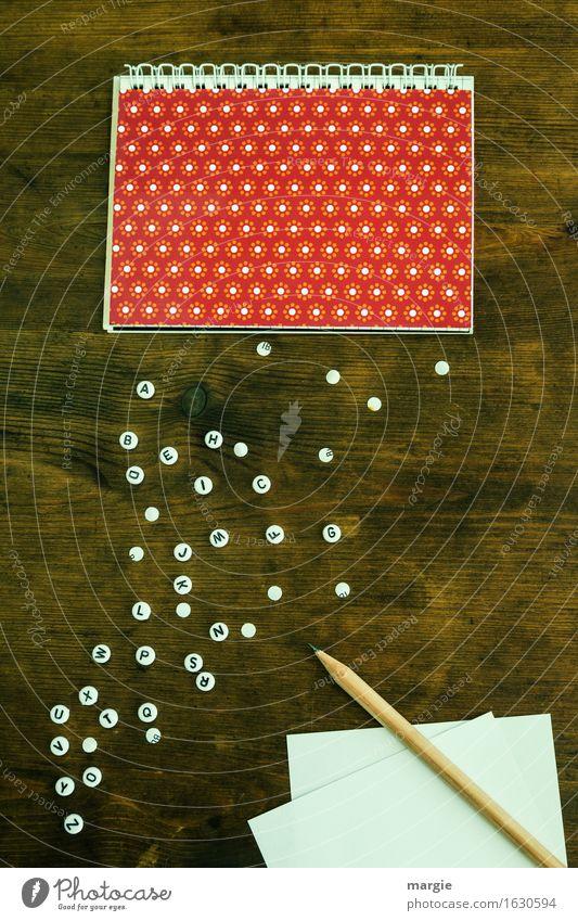 Alphabet ohne Worte:  ein rot - weißer Spiral - Block aus dem weiße Buchstaben fallen. Notizzettel mit Bleistift zum Notieren Arbeit & Erwerbstätigkeit Beruf