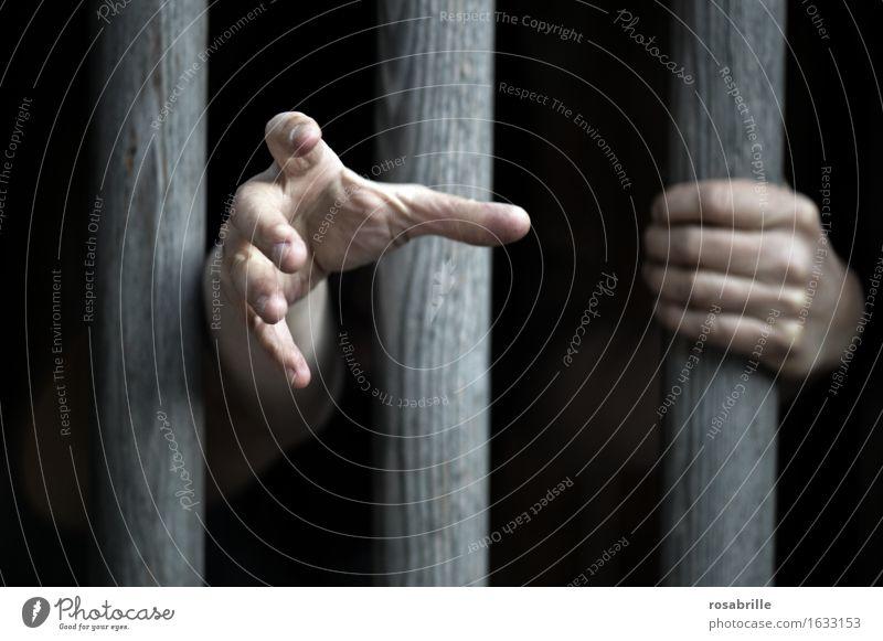 Hände eines eingesperrten Menschen klammern sich an dicke Holzstäbe im Gefängniss und sind Hilfe suchend nach draussen ausgestreckt  um Gnade flehend Hand