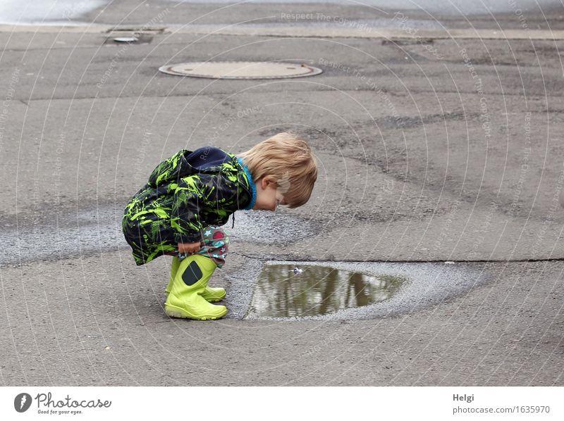 kleiner Junge mit gelben Gummistiefeln und schwarz-gelber Jacke hockt vor einer Pfütze und betrachtet verwundert sein Spiegelbild Mensch maskulin Kleinkind