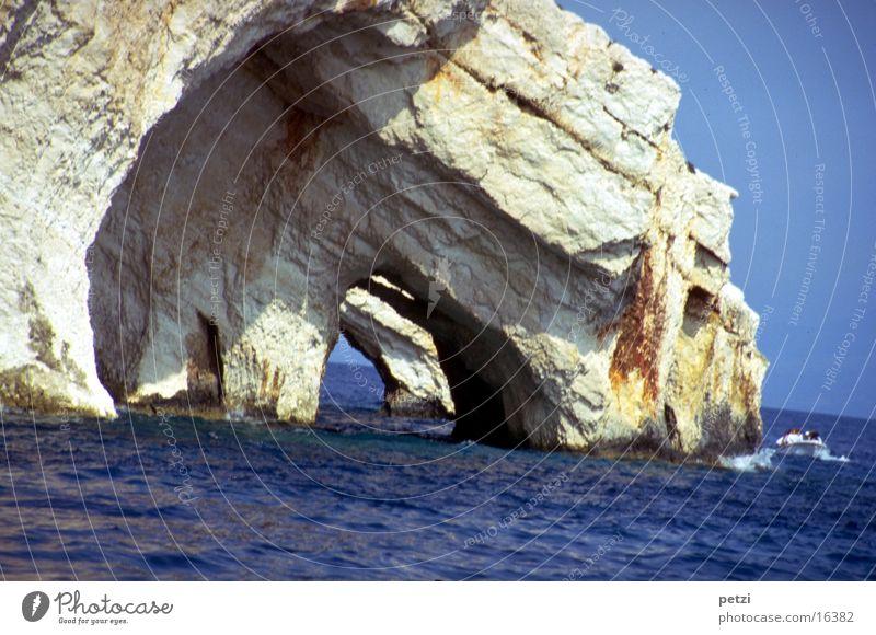 Höhlen im ionischen Meer Wasser Wolkenloser Himmel Sonne Sommer Felsen Wellen Mittelmeer Wasserfahrzeug blau grau Durchblick Gegensätze: fester Fels