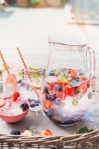 Krug mit Wasser , Beeren und Eiswürfel auf dem Gartentisch Sommer Gesunde Ernährung Wärme Leben Stil Lebensmittel rosa Design Wohnung Frucht Häusliches Leben