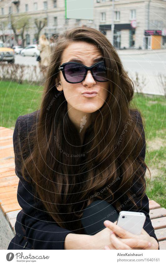 Geschäftsfrau in einem Park, der Gesichter macht. Lifestyle Stil Freude schön Handy Junge Frau Jugendliche 1 Mensch 18-30 Jahre Erwachsene Sommer Stadt Mantel