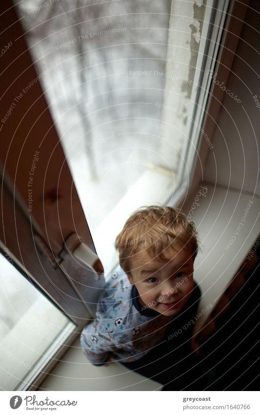 Lächelnder Junge, der auf dem Windowsill sitzt. Winter Kind Baby Kleinkind Mann Erwachsene Kindheit Körper 1 Mensch 1-3 Jahre sitzen stehen träumen warten klein