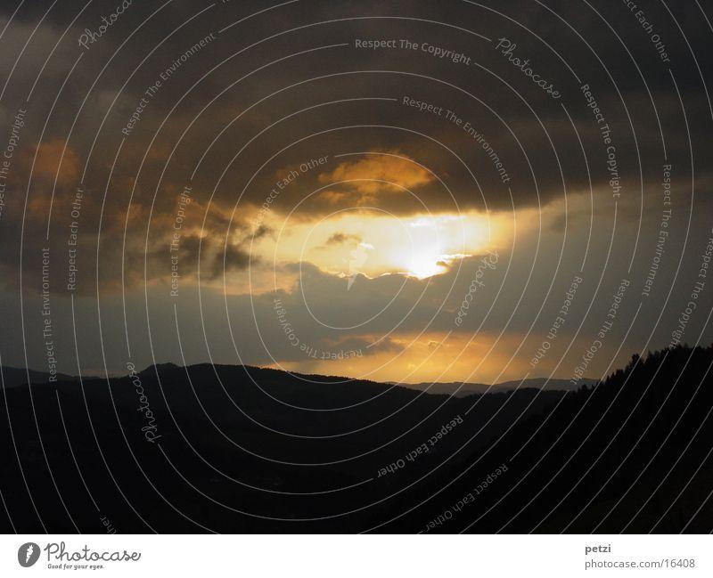 Der Tag geht zu Ende Berge u. Gebirge Wolken Wald gelb grau schwarz Abenddämmerung Sonnenloch Farbfoto Außenaufnahme Textfreiraum oben Textfreiraum unten