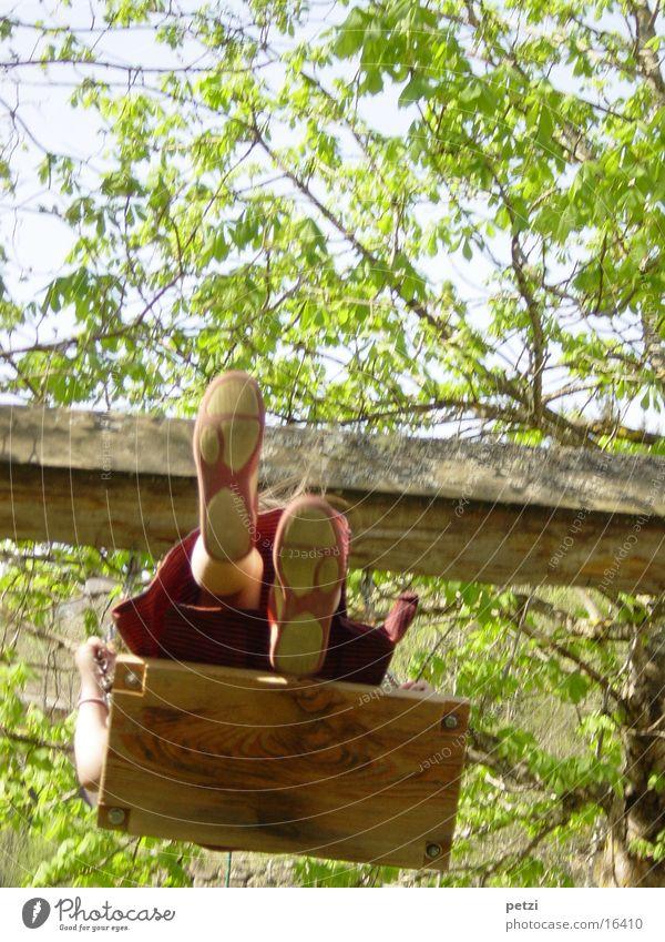 Schaukeln Kind Mensch Beine Schuhe hoch Holzbrett schaukelbrett Farbfoto mehrfarbig Außenaufnahme Froschperspektive