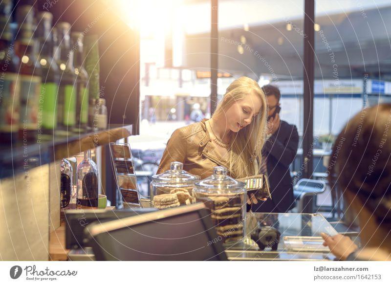 Attraktive blonde Frau, die in einem Geschäft zahlt kaufen Glück Erwachsene bezahlen attraktiv Geldscheine Bar Kantine Kassierer Textfreiraum