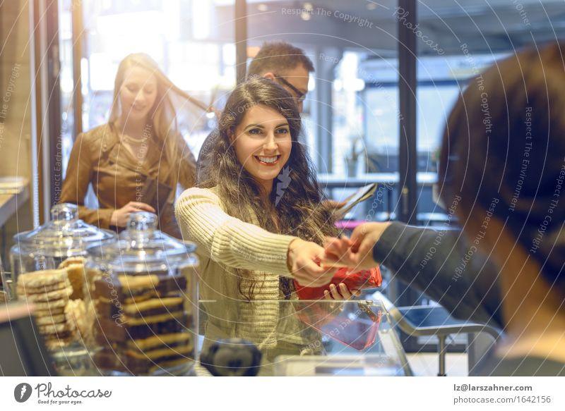 Attraktive junge Frau, die in einem Geschäft zahlt kaufen Glück Erwachsene bezahlen attraktiv Geldscheine Bar Briunette Kantine Kassierer Textfreiraum