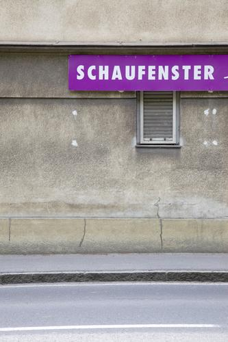 schaufensterschauen Farbfoto Außenaufnahme Menschenleer Tag Zentralperspektive Stadt Stadtrand Haus Gebäude Fenster Straße Schriftzeichen entdecken Blick grau