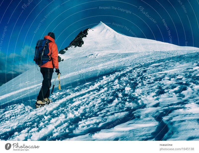 Mountaineer klettert einen schneebedeckten Gipfel. Mensch Ferien & Urlaub & Reisen Mann Landschaft Einsamkeit Berge u. Gebirge Schnee Sport wandern Kraft Erfolg