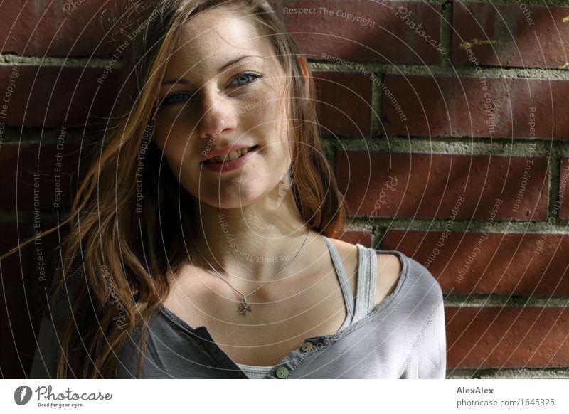 junge Frau steht vor einer Backsteinwand und lächelt - mit Licht und Schattenspiel Haare & Frisuren Gesicht Mauer Junge Frau Jugendliche Sommersprossen