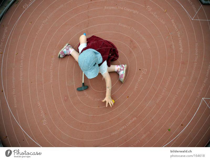 Mini beim Minigolf Farbfoto Außenaufnahme Vogelperspektive Freude Freizeit & Hobby Spielen Minigolfschläger Mensch Kind Mädchen 3-8 Jahre Kindheit Mütze
