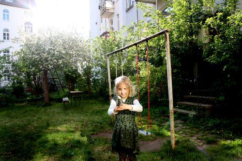 Licht Schuss Kinderspiel Mädchen Frühling Sommer Garten Hinterhof Schaukel Wasserpistole Spielen leuchten Gefühle Stimmung Lebensfreude Freude Idylle Kindheit