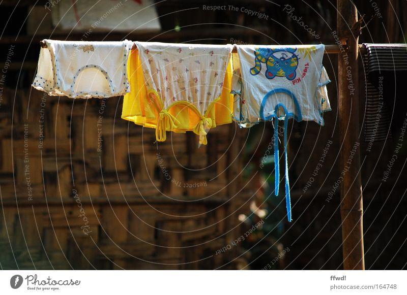Trockenzeit Farbfoto Außenaufnahme Tag Sonnenlicht Schwache Tiefenschärfe Häusliches Leben Asien Dorf Hütte Terrasse Bekleidung T-Shirt Stoff hängen Reinigen