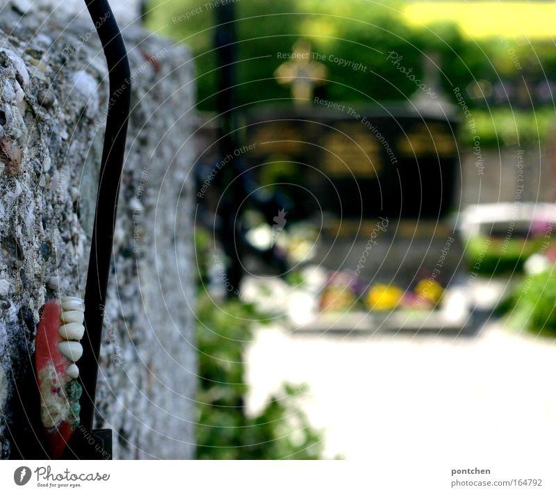Ein verlorenes Gebiss befestigt an einem Kabel an einer Mauer am friedhof. Fundstück. Altern, Tod. Makaber  Grabsteine Und Kreuze im Hintergrund Trauerfeier
