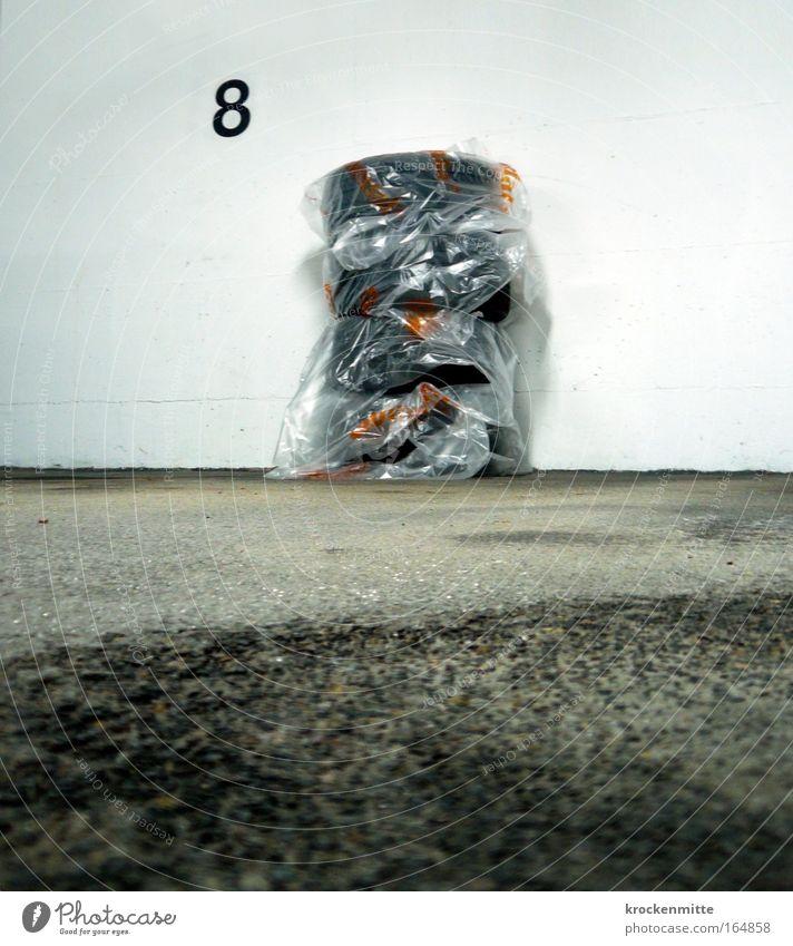 Winterreifenschlaf Farbfoto Innenaufnahme Textfreiraum unten Kunstlicht Froschperspektive Parkhaus Mauer Wand Straßenverkehr Ziffern & Zahlen grau winterreifen