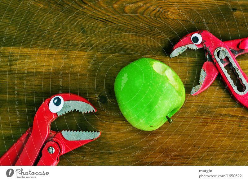 ...schmeckt gut, beiß mal! Zwei Zangen mit Augen beißen in einen grünen Apfel Lebensmittel Frucht Bioprodukte Diät Handwerker Arbeitsplatz Baustelle