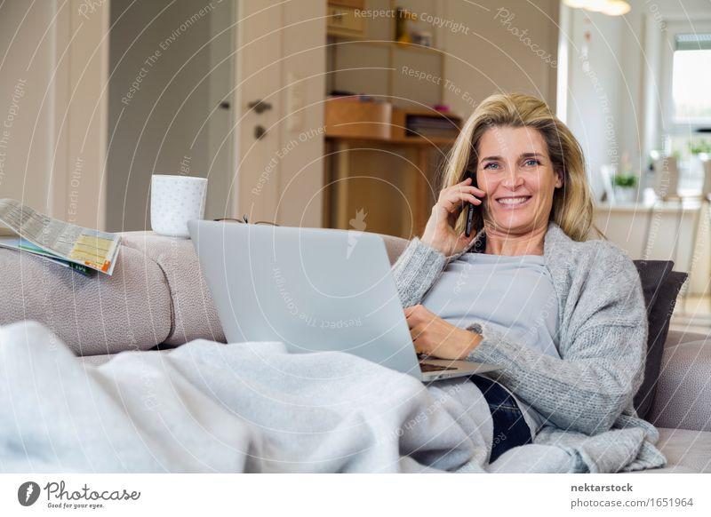 Blonde Frau, die vom Wohnzimmer aus arbeitet. Lifestyle Glück Erholung Freizeit & Hobby Ferien & Urlaub & Reisen Sofa sprechen Telefon Computer Notebook
