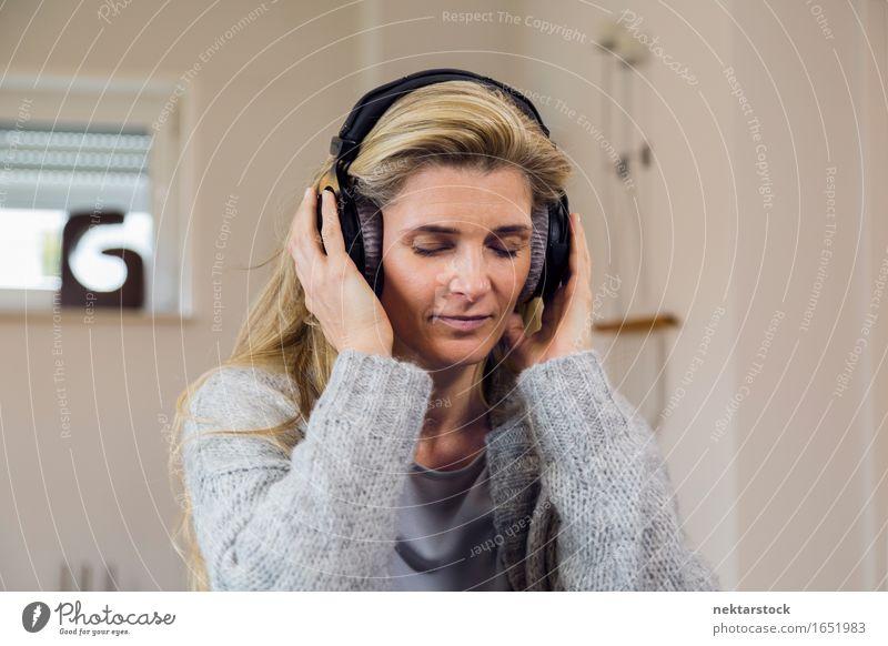 Hübsche blonde Frau, die zu Hause auf der Couch Musik hört. Glück Zufriedenheit Erholung Freizeit & Hobby Entertainment Erwachsene hören Gelassenheit attraktiv
