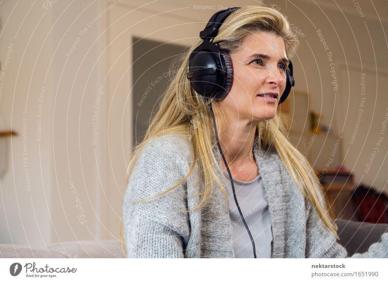 Hübsche blonde Frau, die zu Hause auf der Couch Musik hört. Erholung Freizeit & Hobby Sofa Entertainment Erwachsene hören Lächeln sitzen Fürsorge attraktiv