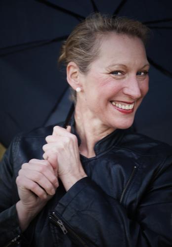 Yvonne feminin 1 Mensch Jacke Ohrringe Regenschirm blond langhaarig Zopf beobachten festhalten Lächeln lachen Blick warten schön Fröhlichkeit Lebensfreude