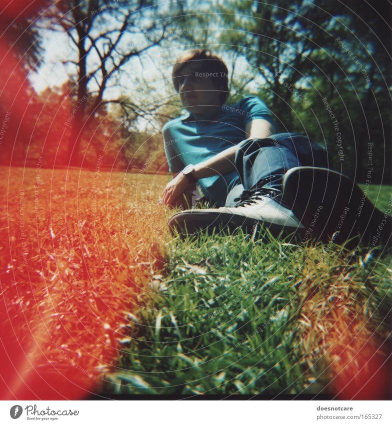 Schiefe Wiese mit jungem Mann und obskuren Lichterscheinungen. Mensch Natur Jugendliche blau grün Baum rot Sommer Erwachsene Erholung Gras Park Schuhe maskulin