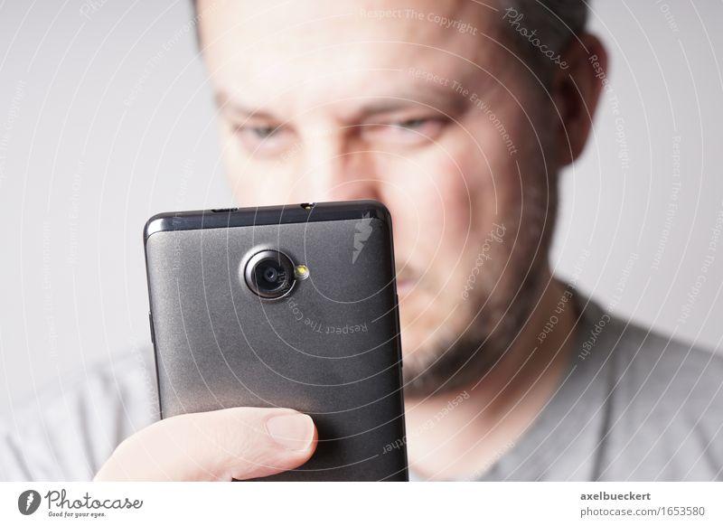 Mann mit Smartphone Mensch Mann Gesicht Erwachsene Lifestyle maskulin Freizeit & Hobby Technik & Technologie lesen Telefon Handy Fotokamera PDA Fotografieren skeptisch Misstrauen