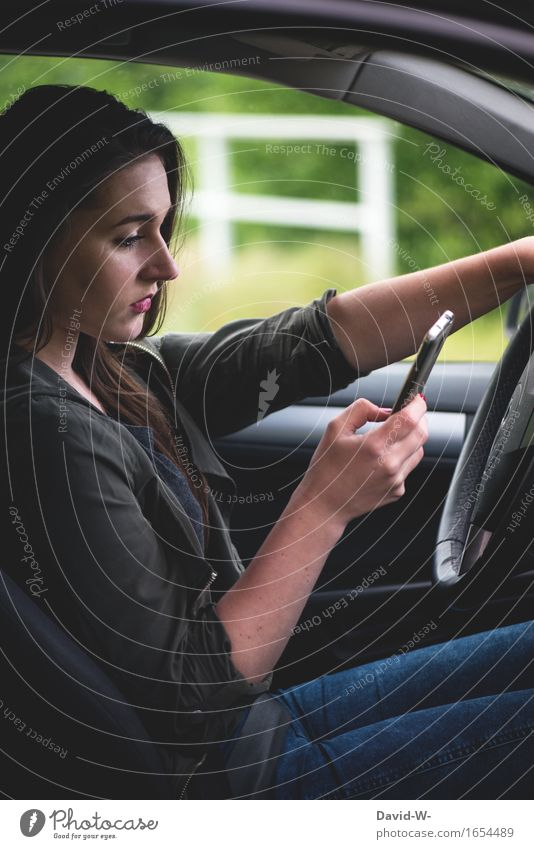 Handy am Steuer Frau jung Auto Autofahren gefahr Abgelenkt gefahrvoll sms whatsapp nachhricht unterschätzt Tippen Wegsehen Risiko Hände Lenkrad Autofenster