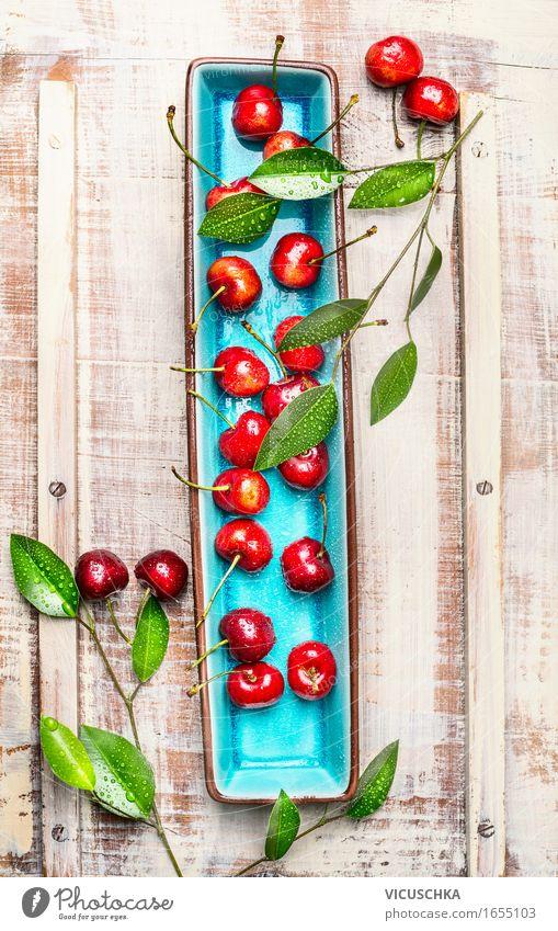 Süße Kirschen mit grünen Blättern auf Platte Lebensmittel Frucht Dessert Ernährung Frühstück Bioprodukte Vegetarische Ernährung Diät Teller Stil