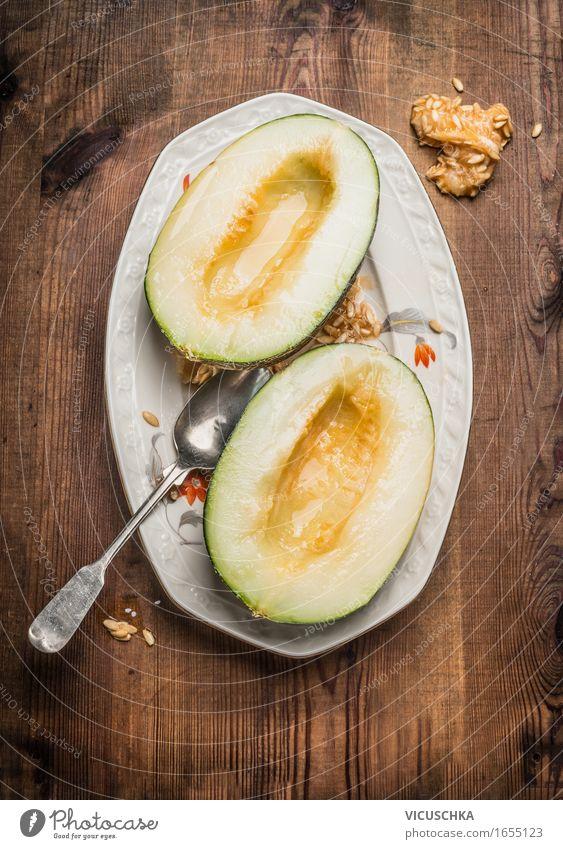 Zwei Hälften der Honig Melone mit Samen und Löffel Lebensmittel Frucht Dessert Ernährung Bioprodukte Vegetarische Ernährung Saft Teller Stil Gesunde Ernährung
