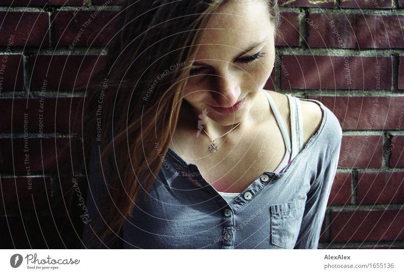 junge Frau lehnt an einer Backsteinmauer und schaut nach unten Glück Junge Frau Jugendliche Kopf Gesicht Sommersprossen 18-30 Jahre Erwachsene Schönes Wetter
