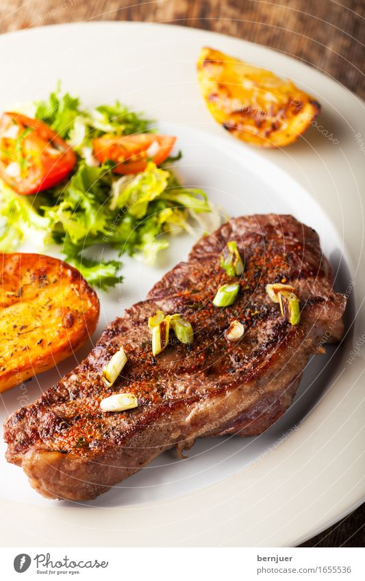Gegrilltes Steak mit gerösteten Kartoffeln dunkel lecker Medien Restaurant Teller Fleisch Abendessen Mittagessen Tomate saftig fein Porree gebraten Rindfleisch