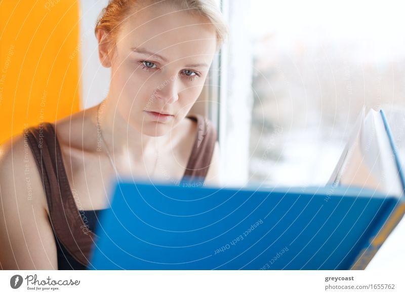 Junge Frau, die ein Buch mit blauer Abdeckung liest Mensch Jugendliche schön weiß Erholung Einsamkeit Haus Mädchen 18-30 Jahre Erwachsene Lifestyle Glück Schule
