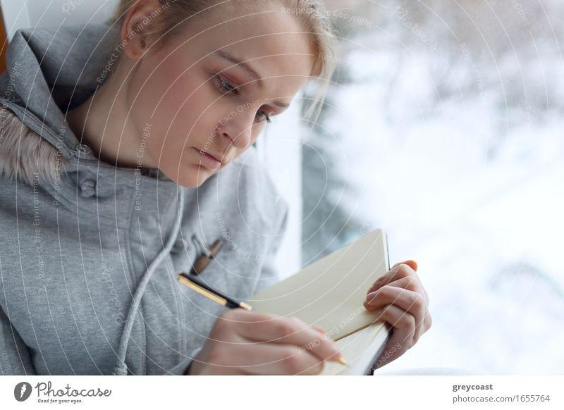 Junges Mädchen schreibt in ihr Tagebuch, während sie an einem großen Fenster sitzt. Windstille lesen Winter Bildung Schüler Student Büro Junge Frau Jugendliche