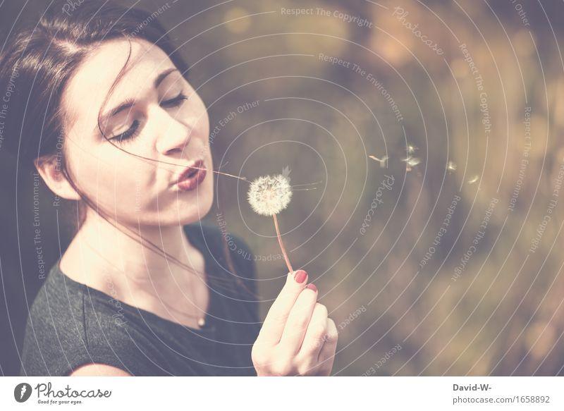 junge hübsche Frau pustet an einer Pusteblume und lässt die Samen umherfliegen pusten Löwenzahn Mund Gesicht Sommer sommerlich