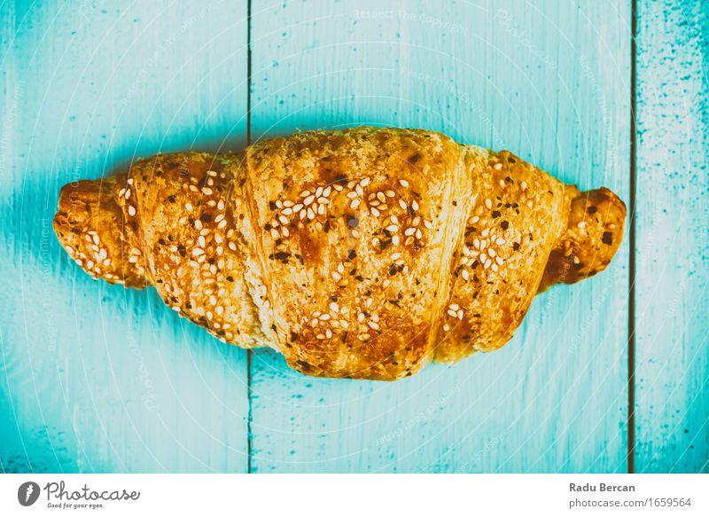 Croissant auf blauem Tisch Lebensmittel Ernährung Essen Frühstück füttern einfach nah süß mehrfarbig gelb gold türkis Holztisch Wald Französisch Backwaren Snack