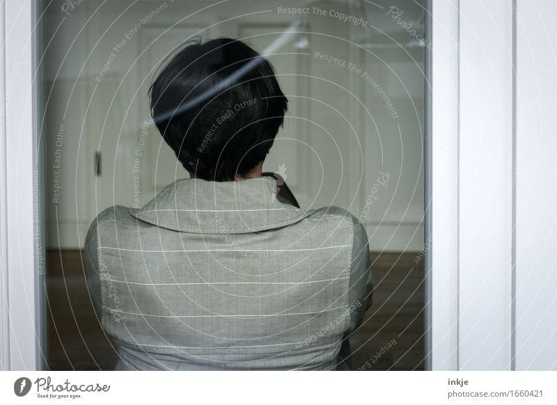 warten Lifestyle Häusliches Leben Glasscheibe Glastür Frau Erwachsene Kopf Rücken 1 Mensch Mantel hocken sitzen Gefühle Stimmung Ausdauer Langeweile Einsamkeit
