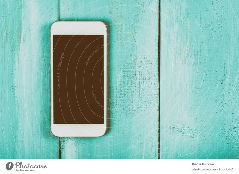Weißer Handy mit leerem Bildschirm auf hölzerner Tabelle blau Farbe weiß schwarz Mode Textfreiraum Kommunizieren Technik & Technologie Telekommunikation Tisch