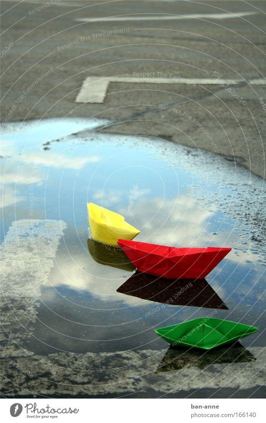 Schiffbruch Farbfoto Menschenleer Tag Wasser nass gelb grün rot Freude Papier Papierschiff Spielen Reflexion & Spiegelung See Parkplatz Pfütze Im Wasser treiben