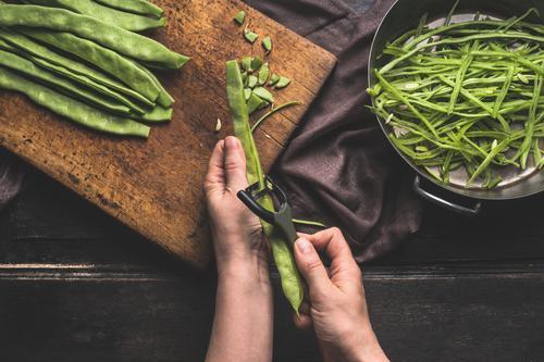Weibliche Hände schneiden Bohnen mit Gemüseschäler . Lebensmittel Ernährung Mittagessen Abendessen Bioprodukte Vegetarische Ernährung Diät Topf Messer Stil