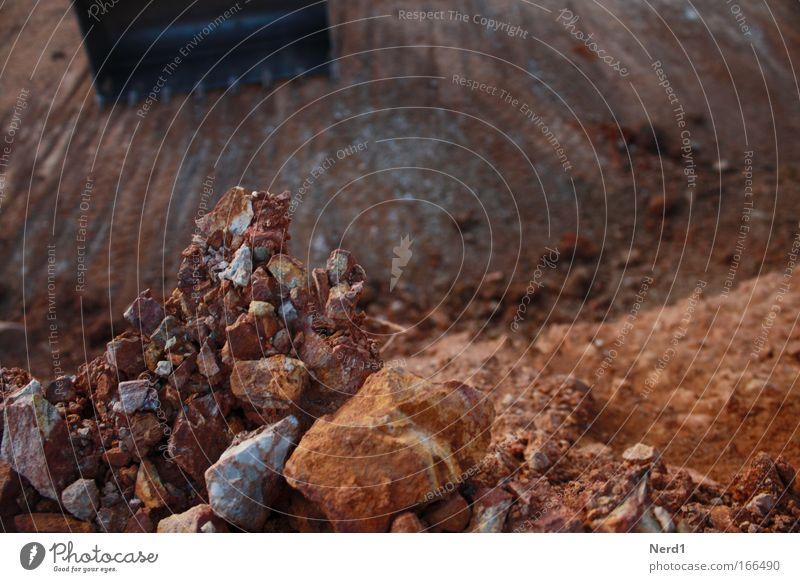 Schaufelbagger Farbfoto Außenaufnahme Detailaufnahme Menschenleer Kontrast Sonnenlicht Schwache Tiefenschärfe Baustelle Maschine Fahrzeug Stein Bruchstein