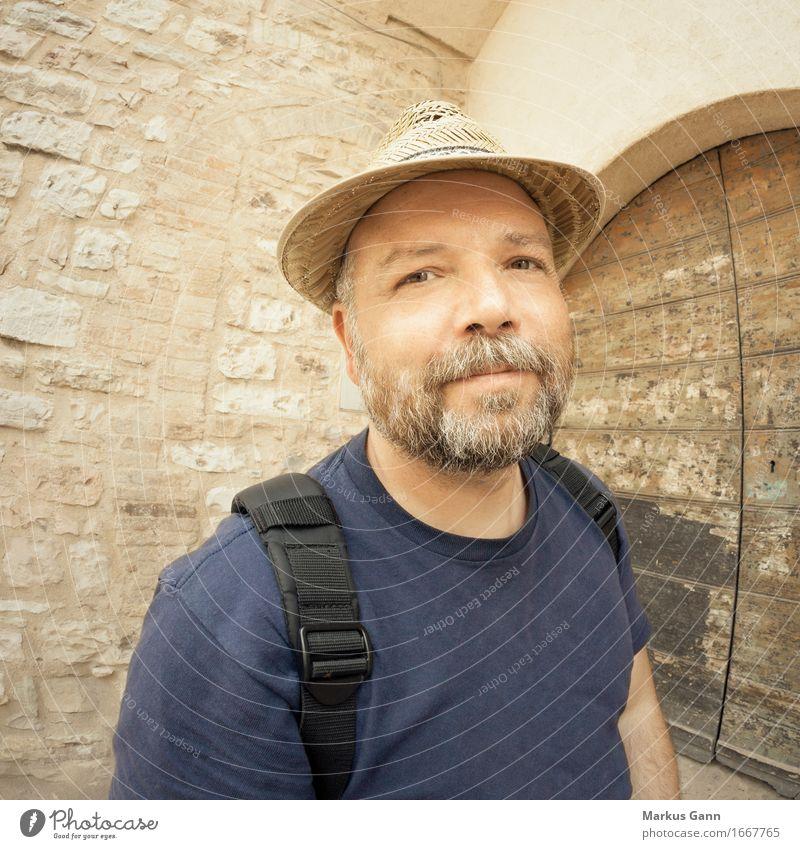 Mann mit Bart und Strohut ruhig Wand Mauer braun Tür T-Shirt Hut grinsen Vollbart beige Rucksack sympathisch Strohhut