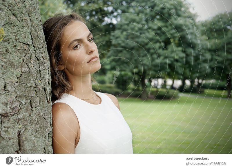 traurige junge Frau, die am Baum sich lehnt Lifestyle Freizeit & Hobby Mensch Junge Frau Jugendliche Erwachsene 1 18-30 Jahre Natur Park träumen Traurigkeit