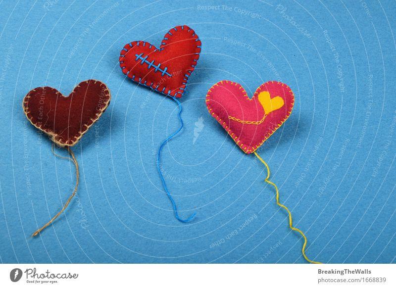 Drei Spielzeugherzen mit den Threads, rot, rosa und braun auf Blau blau gelb Liebe Kunst Zusammensein Freizeit & Hobby Kreativität Herz Geschenk Romantik Wolle