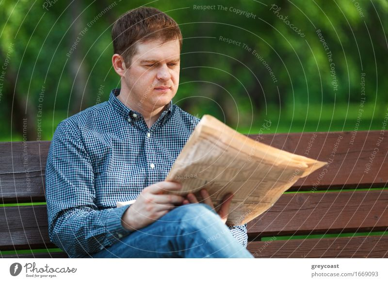 Mann liest Zeitung auf Bank im Park Lifestyle Glück Erholung lesen Garten Business Mensch Junger Mann Jugendliche Erwachsene 1 18-30 Jahre Zeitschrift Papier