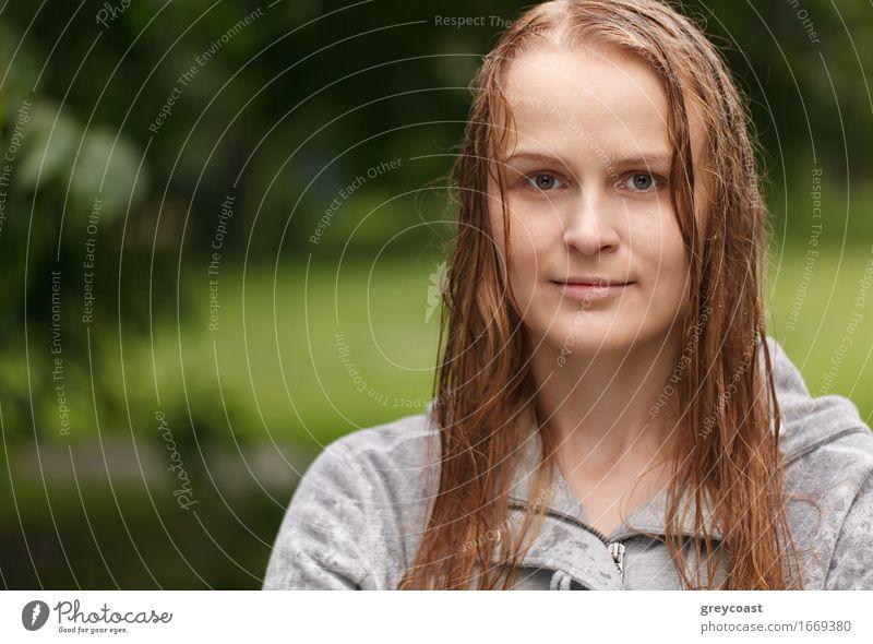 Porträt eines Mädchens, das nach dem Regen im Park zum Fotografen schaut, mit Kopierraum auf der linken Seite. Lifestyle Glück schön Gesicht Sommer Mensch