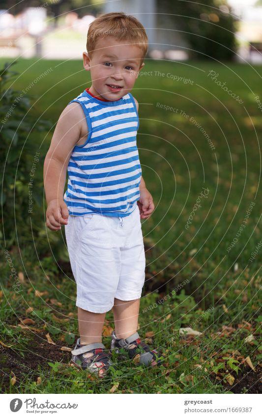 Porträt von 3 Jahre altem Jungen in gestreifter Weste im Stadtpark, der zum Fotografen schaut und lächelt Lifestyle Freude Glück schön Gesicht Freizeit & Hobby