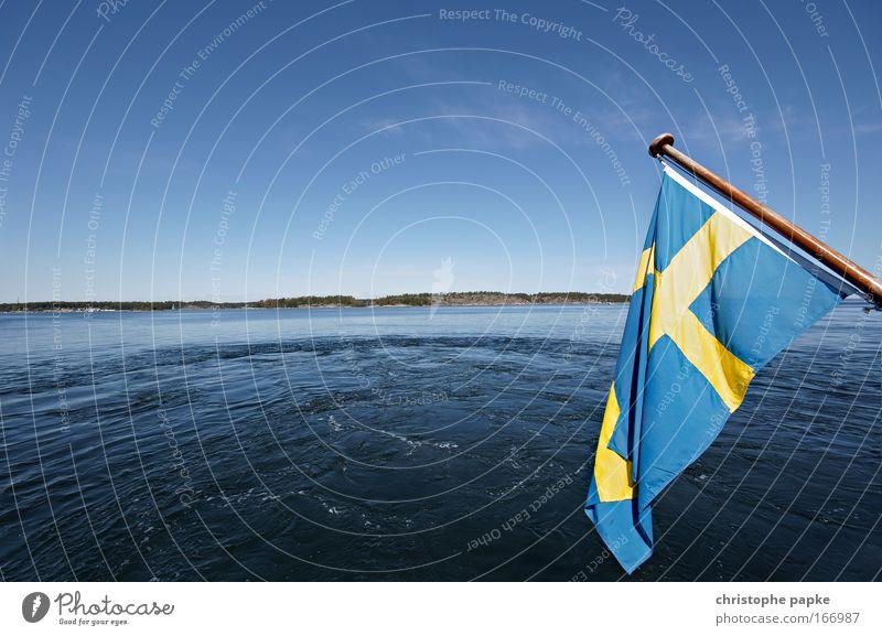 Schwedische Flagge, im HIntergrund Wasser und Inseln der Schären vor Stockholm Schweden Fahne Schärengarten Skandinavien Landschaft Fjord Ausflug Seeufer