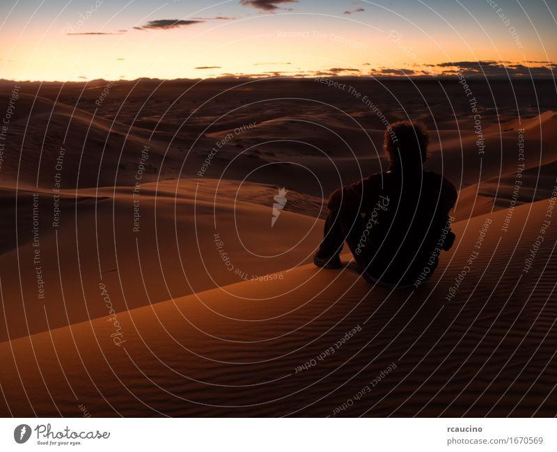 Bemannen Sie das Sitzen auf einer Düne in der Wüste beim Überwachen des Sonnenuntergangs schön Erholung Meditation Ferien & Urlaub & Reisen Tourismus Ausflug