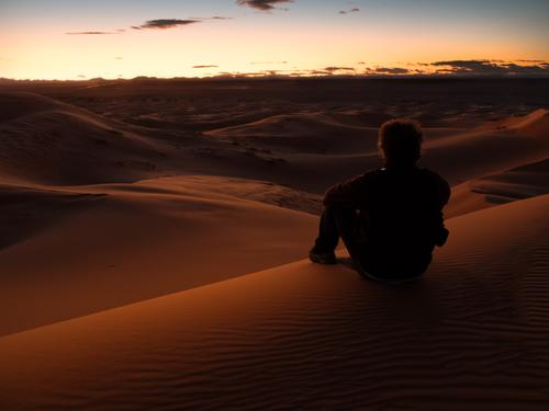 Bemannen Sie das Sitzen auf einer Düne in der Wüste beim Überwachen des Sonnenuntergangs Mensch Natur Ferien & Urlaub & Reisen Mann Sommer schön Farbe
