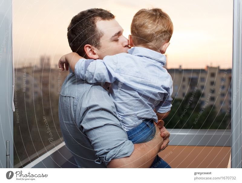 Dreißig Jahre alter Vater küsst seinen dreijährigen Sohn auf dem Balkon Lifestyle Freude Glück Gesicht Ferien & Urlaub & Reisen Sonne Kindererziehung Mensch